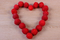 新鲜的莓的心脏在木桌上的,爱的标志 库存照片