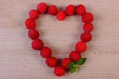 新鲜的莓的心脏在木桌上的,爱的标志 免版税图库摄影