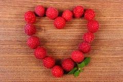新鲜的莓的心脏在木桌上的,爱的标志 图库摄影