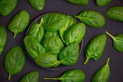 新鲜的菠菜在碗离开在黑暗的背景 顶视图 库存照片