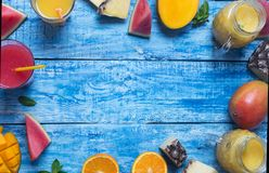 新鲜的菠萝、芒果和西瓜鸡尾酒在两块玻璃中用在蓝色木土气背景,拷贝空间的果子 库存照片