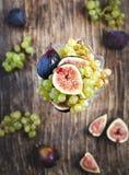 新鲜的葡萄和无花果在花瓶 免版税库存照片