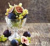 新鲜的葡萄和无花果在花瓶 库存图片