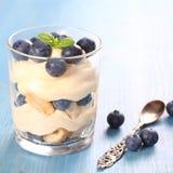 新鲜的蓝莓分层了堆积有mascarpone奶油和曲奇饼的沙漠 图库摄影