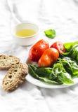 新鲜的蓬蒿、蕃茄在一块白色板材,橄榄油和长方形宝石 库存图片