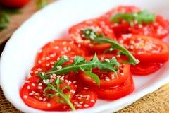 新鲜的蕃茄切片、芝麻菜火箭和芝麻籽沙拉 在一块白色板材和粗麻布餐巾的低热值沙拉 饮食午餐 库存图片