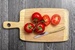 新鲜的蕃茄和刀子顶视图在砧板 免版税库存图片
