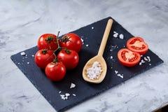 新鲜的蕃茄和盐匙子在黑人石委员会的在白色背景,特写镜头,选择聚焦 免版税库存图片