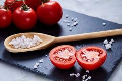 新鲜的蕃茄和盐匙子在黑人石委员会的在白色背景,特写镜头,选择聚焦 图库摄影