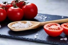 新鲜的蕃茄和盐匙子在黑人石委员会的在白色背景,特写镜头,选择聚焦 库存照片