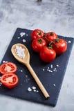 新鲜的蕃茄和盐匙子在黑人石委员会的在白色背景,特写镜头,选择聚焦 库存图片