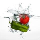 新鲜的蕃茄和胡椒飞溅在白色Backgr隔绝的水中 免版税库存照片