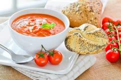 新鲜的蕃茄汤和新被烘烤的有壳的小圆面包 免版税库存照片