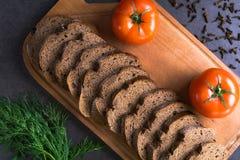 新鲜的蕃茄用家制面包和绿色,在木板的谎言 图库摄影