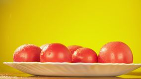 新鲜的蕃茄落与水滴在板材的 营养的概念 在黄色背景的孤立,减速 影视素材