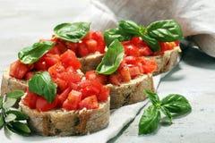 新鲜的蕃茄bruschetta 与蓬蒿的意大利食物开胃菜 免版税库存图片