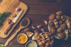 新鲜的蘑菇用香料和草本在一个木板作为成份 免版税图库摄影