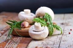 新鲜的蘑菇用香料和草本在老木板 免版税库存照片
