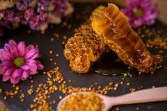 新鲜的蜂窝和花粉在桌上 免版税库存照片
