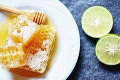 新鲜的蜂蜜和柠檬石灰/关闭在白色板材的黄色甜蜂窝切片 库存图片