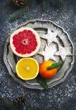 新鲜的被分类的柑橘水果和圣诞节曲奇饼在板材 免版税库存图片