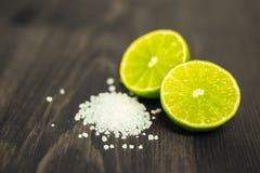 新鲜的被切的石灰、柠檬和盐在木桌上 免版税库存图片