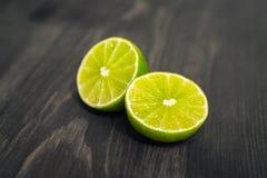 新鲜的被切的石灰、柠檬和盐在木桌上 图库摄影