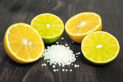 新鲜的被切的石灰、柠檬和盐在木桌上 库存图片