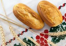 新鲜的被烘烤的小圆面包和麦子的金黄耳朵在传统桌布的 库存照片