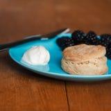 新鲜的被烘烤的烤饼用奶油和莓果果酱 库存照片