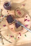 新鲜的被烘烤的自创健康面包用黑醋栗果酱-自创橘子果酱用从庭院的新鲜的有机果子 在土气12月 免版税库存照片