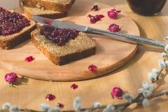 新鲜的被烘烤的自创健康面包用黑醋栗果酱-自创橘子果酱用从庭院的新鲜的有机果子 在土气12月 图库摄影