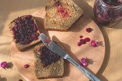 新鲜的被烘烤的自创健康面包用黑醋栗果酱-自创橘子果酱用从庭院的新鲜的有机果子 在土气12月 库存照片