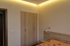 新鲜的被更新的公寓的卧室与现代LED照明设备 免版税库存照片