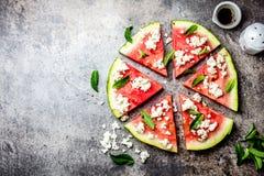 新鲜的西瓜薄饼沙拉用希腊白软干酪、薄菏、盐和油在石背景 免版税库存照片