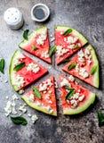 新鲜的西瓜薄饼沙拉用希腊白软干酪、薄菏、盐和油在石背景 库存图片