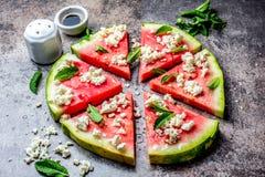 新鲜的西瓜薄饼沙拉用希腊白软干酪、薄菏、盐和油在石背景 库存照片
