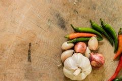 新鲜的辣椒、大蒜和青葱在一个圈子在木 库存照片