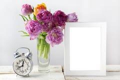 新鲜的郁金香开花花束和空白的照片框架与拷贝空间在木背景 库存图片