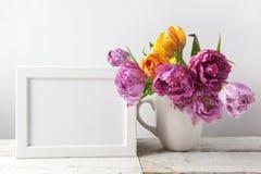 新鲜的郁金香开花花束和空白的照片框架与拷贝空间在木背景 免版税库存照片