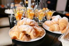 新鲜的酥皮点心,酥脆早晨新月形面包,旅馆早餐自助餐 点心在杯子的水果鸡尾酒 免版税库存图片