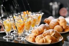 新鲜的酥皮点心,酥脆早晨新月形面包,旅馆早餐自助餐 点心在杯子的水果鸡尾酒 免版税库存照片