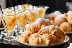 新鲜的酥皮点心,酥脆早晨新月形面包,旅馆早餐自助餐 点心在杯子的水果鸡尾酒 图库摄影