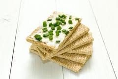 新鲜的酥脆面包用酸奶干酪和大葱在一张白色木桌上 饮食的早餐 免版税库存图片