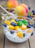 新鲜的酸奶干酪用桃子、蓝莓、杏仁和蜂蜜 库存照片