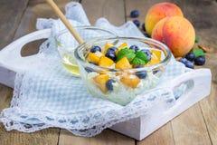 新鲜的酸奶干酪用桃子、蓝莓、杏仁和蜂蜜 免版税图库摄影