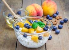 新鲜的酸奶干酪用桃子、蓝莓、杏仁和蜂蜜 免版税库存图片