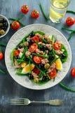 新鲜的金枪鱼青豆沙拉用鸡蛋,蕃茄,豆,在白色板材的橄榄 概念健康食物 库存照片