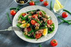 新鲜的金枪鱼青豆沙拉用鸡蛋,蕃茄,豆,在白色板材的橄榄 概念健康食物 免版税库存图片