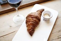 新鲜的面包店新月形面包和杯红葡萄酒在木桌里 城市在窗口附近的咖啡馆白天 免版税库存照片